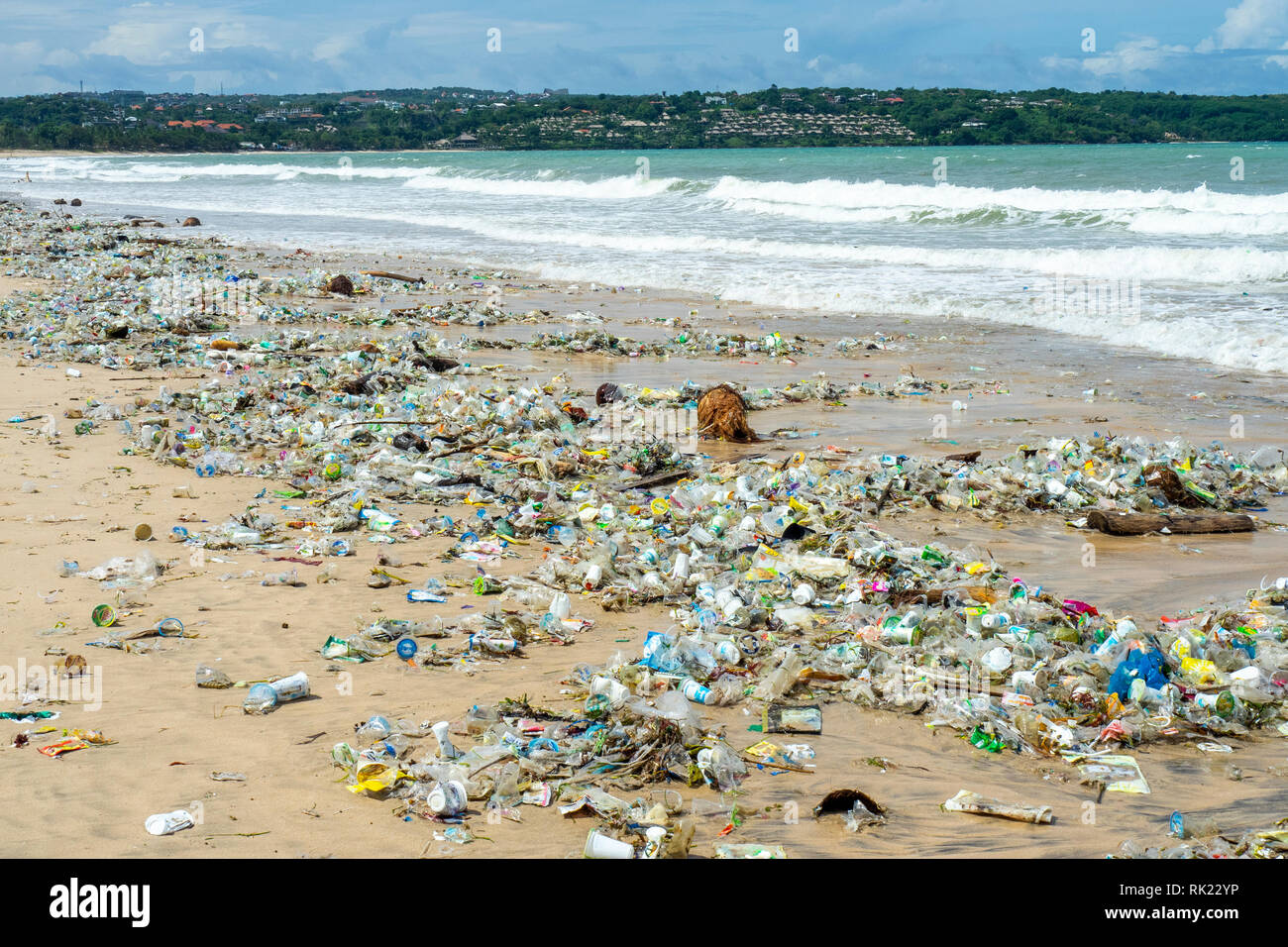 Pollution of plastic bottles, cups, straws and other litter washing up on the beach at Jimbaran Bay, Bali Indonesia. Stock Photo