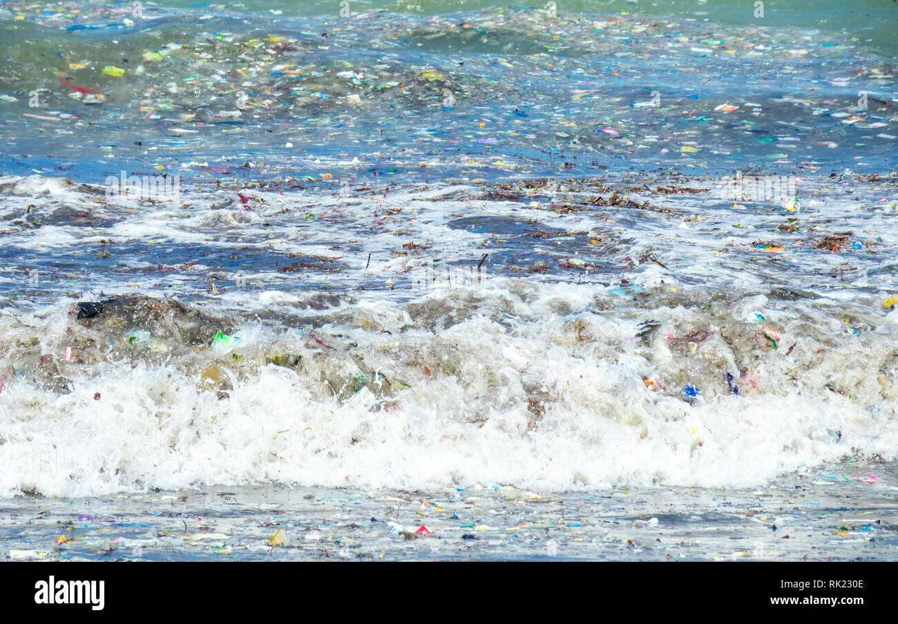 pollution-of-plastic-bottles-cups-straws-and-other-litter-washing-up-on-the-beach-at-jimbaran-bay-bali-indonesia-RK230E.jpg