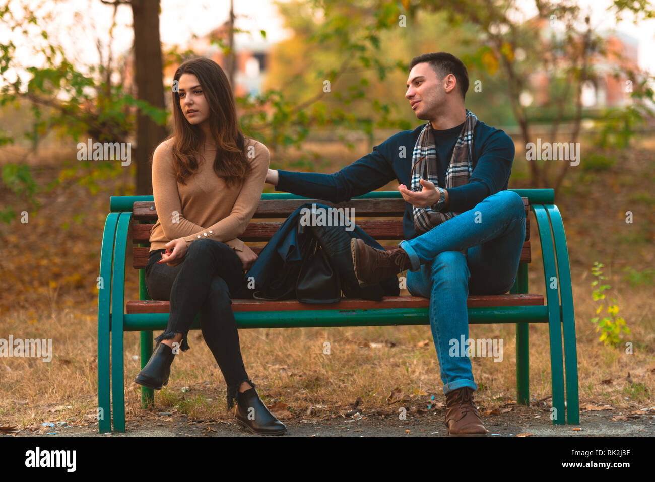 Angry girlfriend  ignoring her boyfriend while he is trying to apologize. Stock Photo
