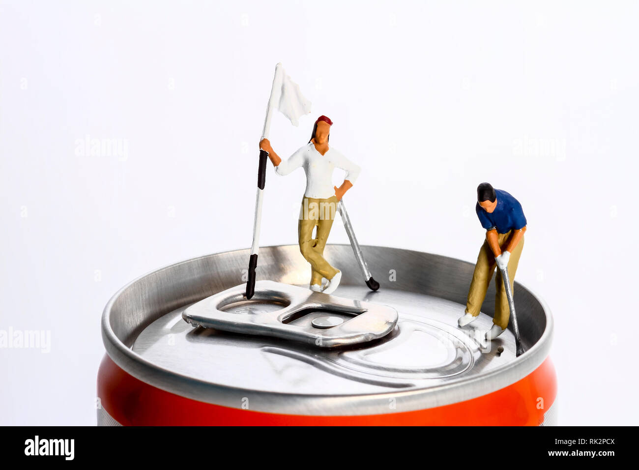 Conceptual diorama image of a miniture figure couple playing golf on a drinks can Stock Photo