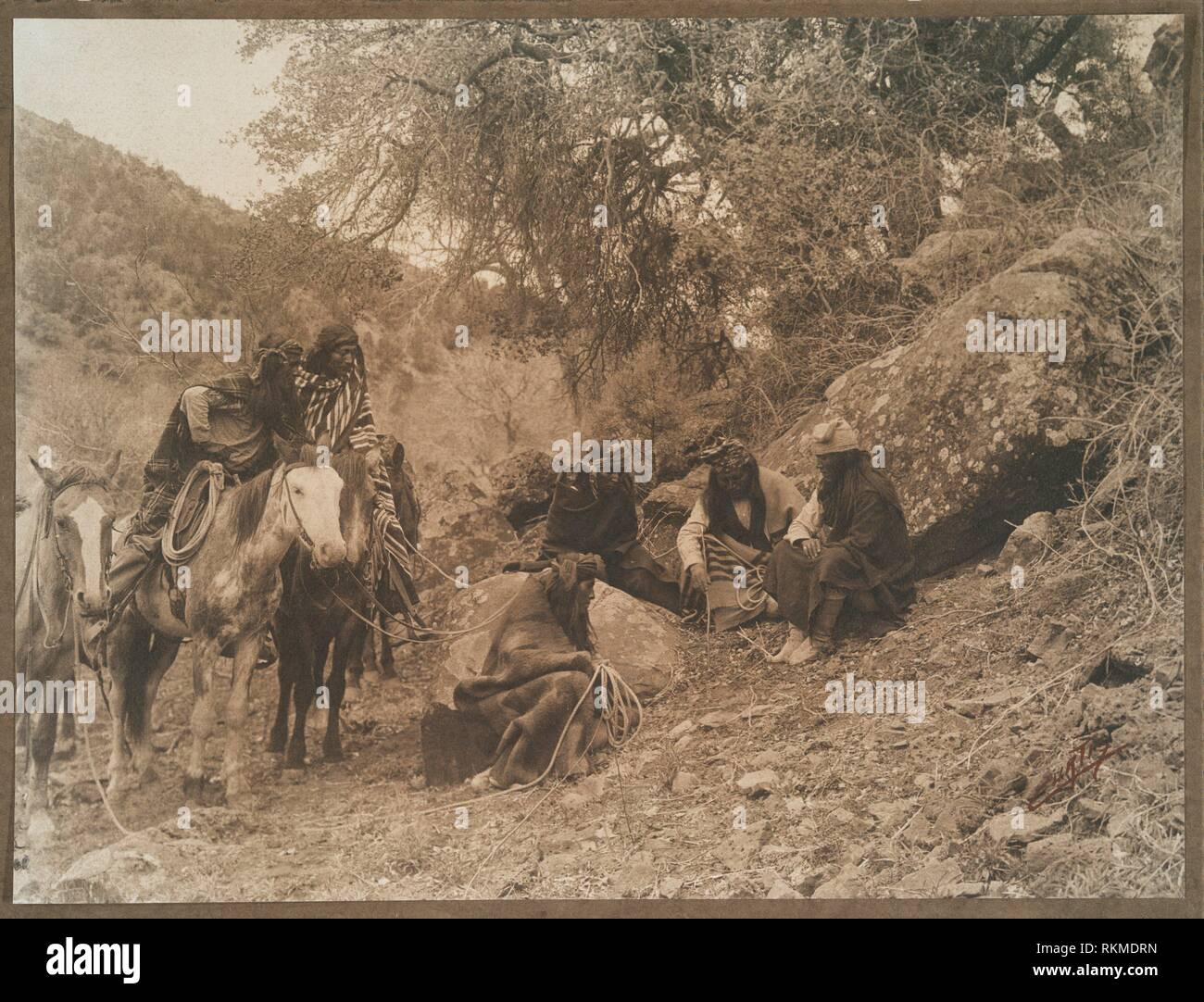 Apaches. Additional title: A story telling group of White Mountain Apaches. Curtis, Edward S., 1868-1952 (Photographer). Indian photographs. Date Stock Photo