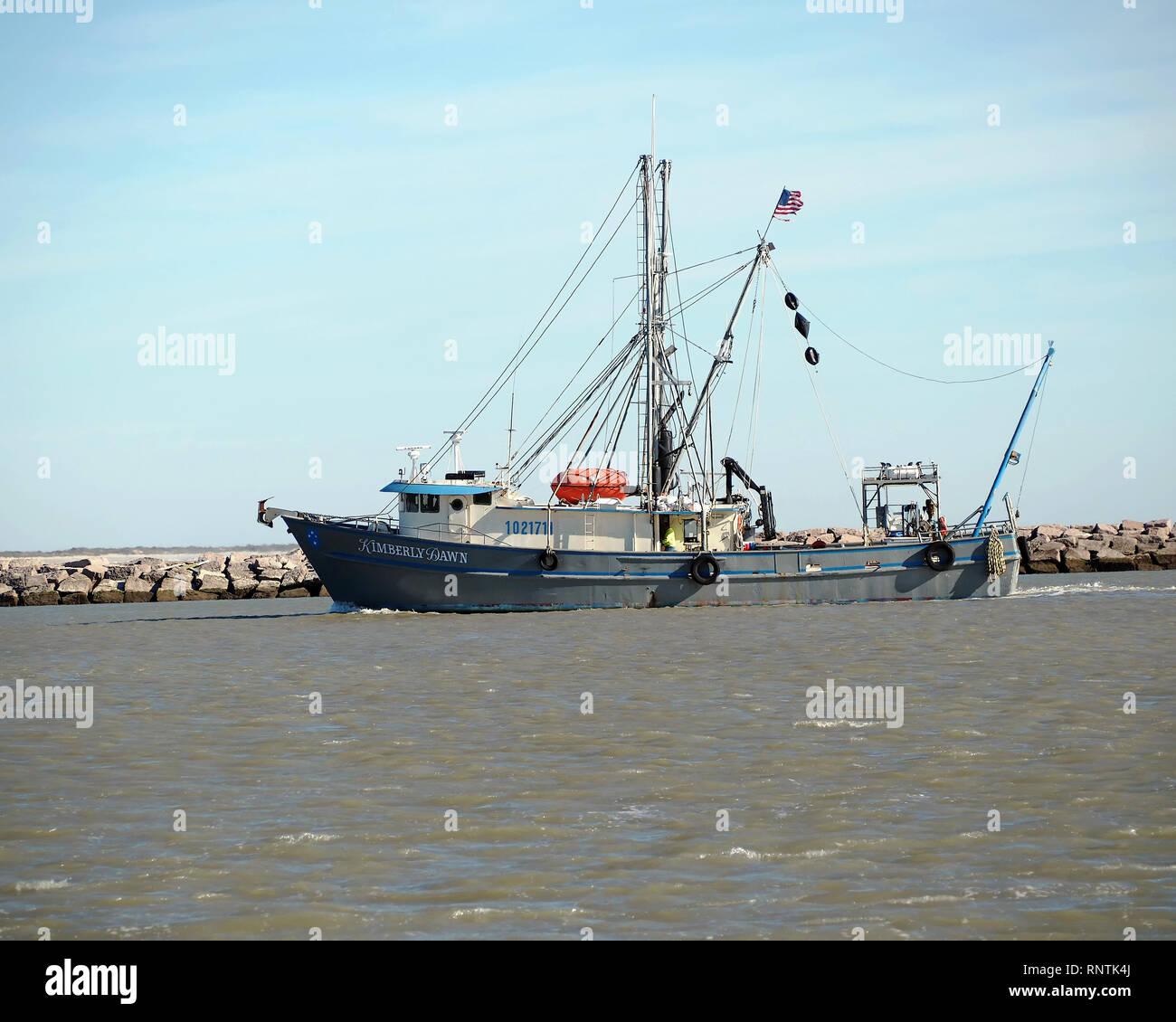 "The shrimp boat, "" Kimberly Dawn,"" passes through the Corpus Christi Ship Channel near the north jetty in Port Aransas, Texas USA. Stock Photo"