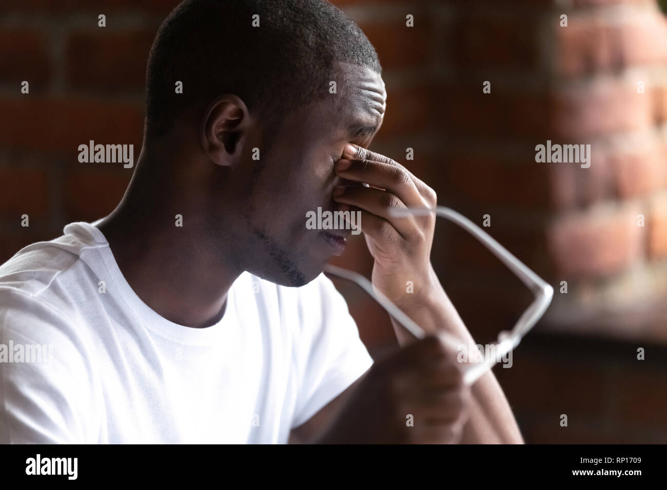 Close up black students take off glasses massaging eyes Stock Photo