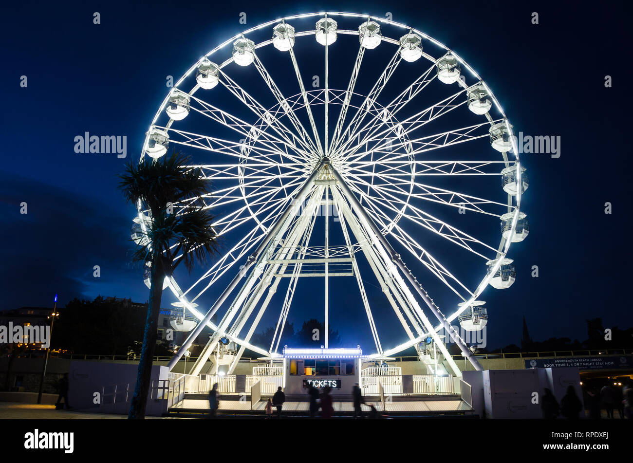 The big wheel at Bournemouth stands tall into the night sky and is brightly lit up white. Stock Photo