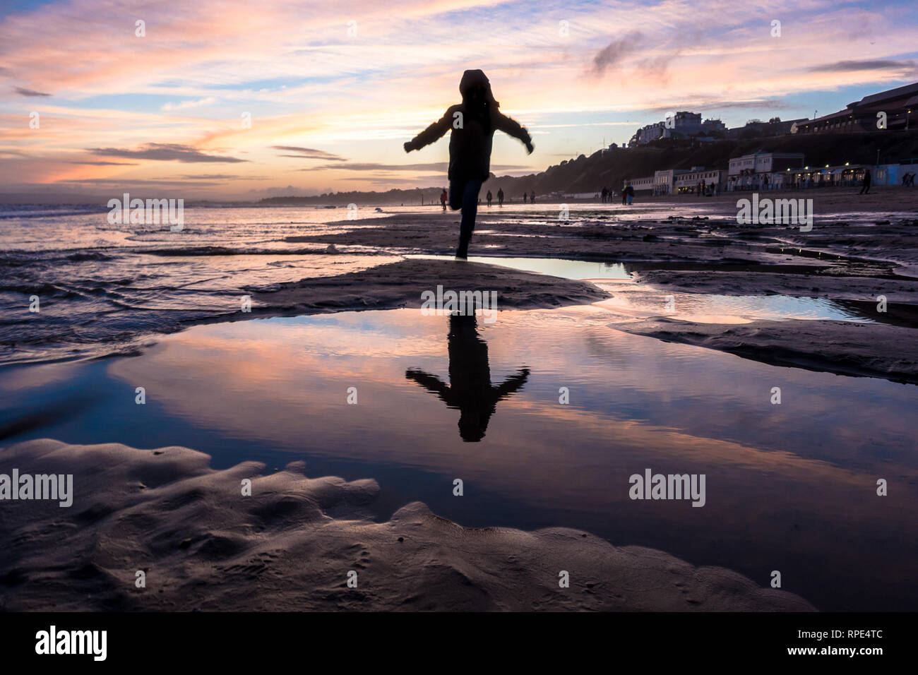 bright-orange-sunset-at-the-beach-at-bournemouth-as-a-young-boy-runs-and-jumps-over-pools-of-water-left-in-the-sand-RPE4TC.jpg