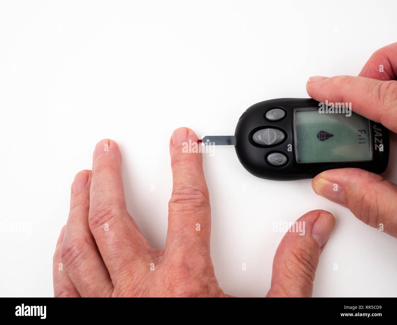 Testing glucose level with electronic meter and test strip after lancet has drawn blood sample from Type 2 diabetics finger Stock Photo