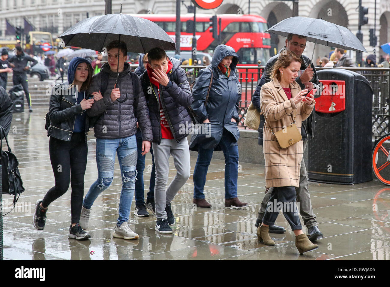 London, UK. 6th Mar, 2019. Tourists shelter from the rain beneath umbrellas as it starts raining in the capital. Credit: Dinendra Haria/Alamy Live News Stock Photo