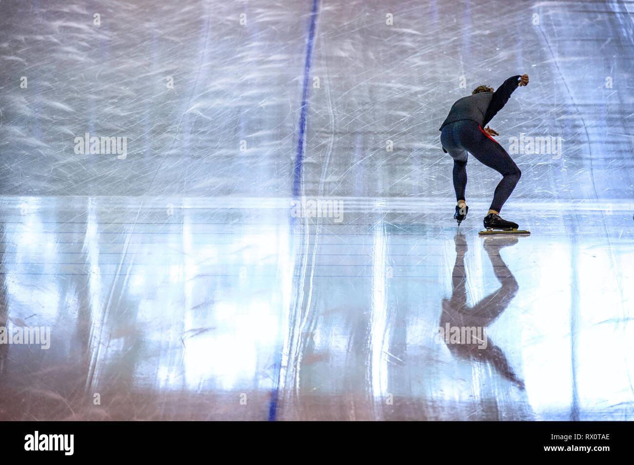Athletic speed skater in training, practicing at the start line of a speed skating oval Stock Photo