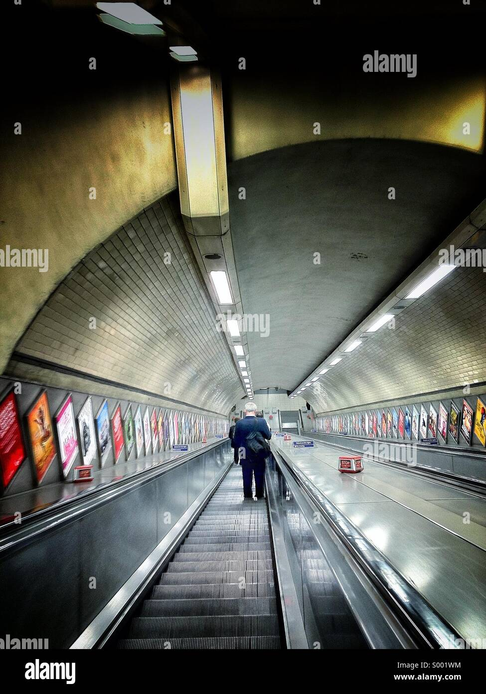 Commuter going down the stairs at Kentish Town Underground Station - Stock Image
