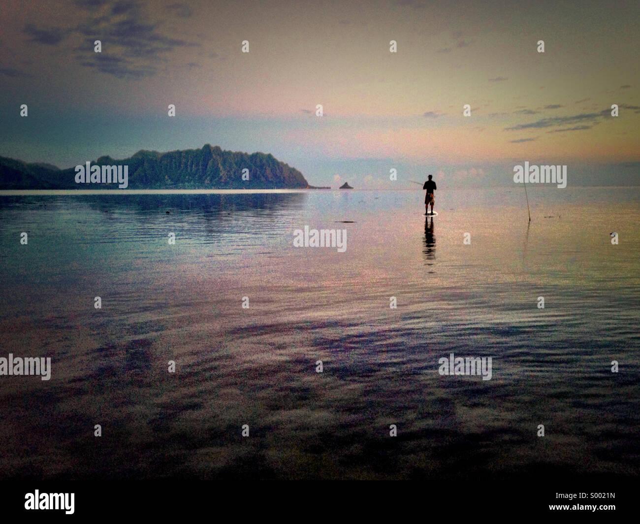 Stand up board fishing at Kaneohe Bay, Oahu, Hawaii. Kualoa Koolau mountains as backdrop. - Stock Image