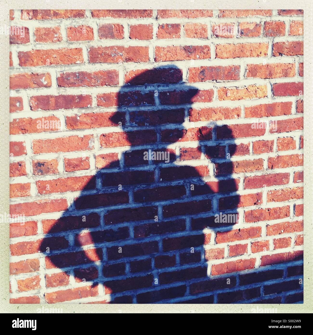 The shadow of a man against a brick wall - Stock Image