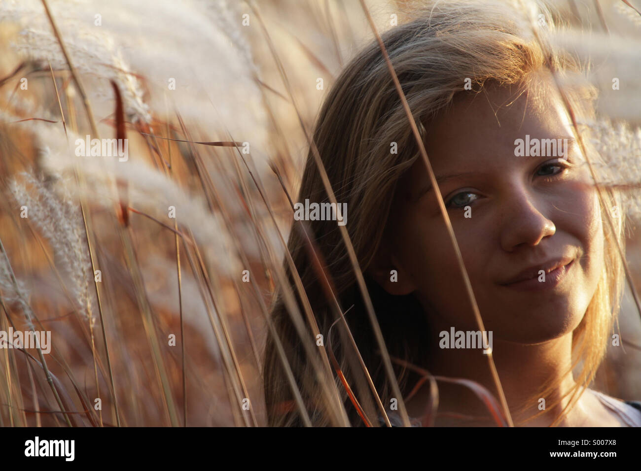 A young woman walks through Autumn grasses. - Stock Image