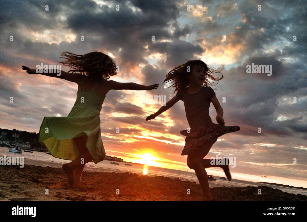 Girls whirl on the sand at sunset on the beach in devon, UK - Stock Image