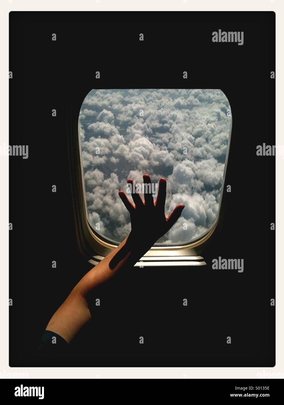 Boy touching window of airplane in flight with clouds in view. - Stock Image
