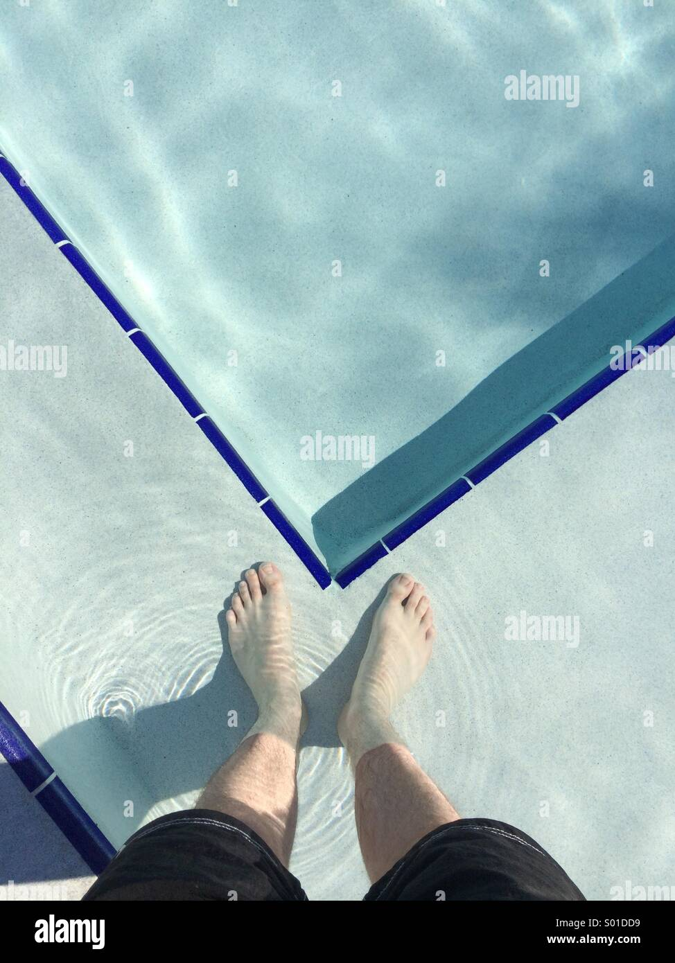 A selfie in a swimming pool. Looking down at a man's feet standing in a pool in Florida, USA. - Stock Image