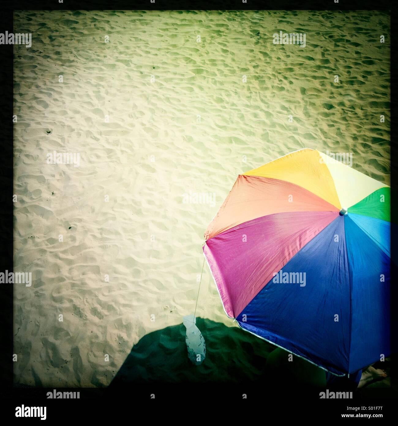 Umbrella on a sandy beach - Stock Image