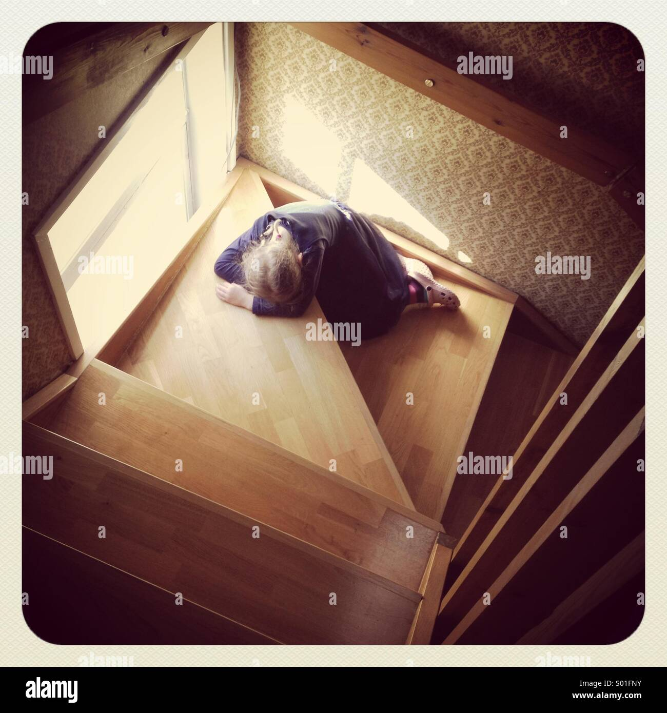 A young girl asleep or upset on some old fashioned wooden stairs - Stock Image