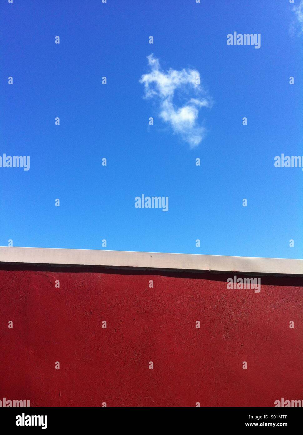 Red wall and blue sky with cloud - Stock Image