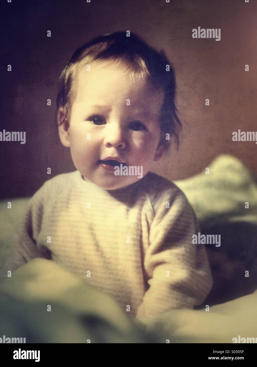 Baby aged 9-12 months sitting on bed - Stock Image