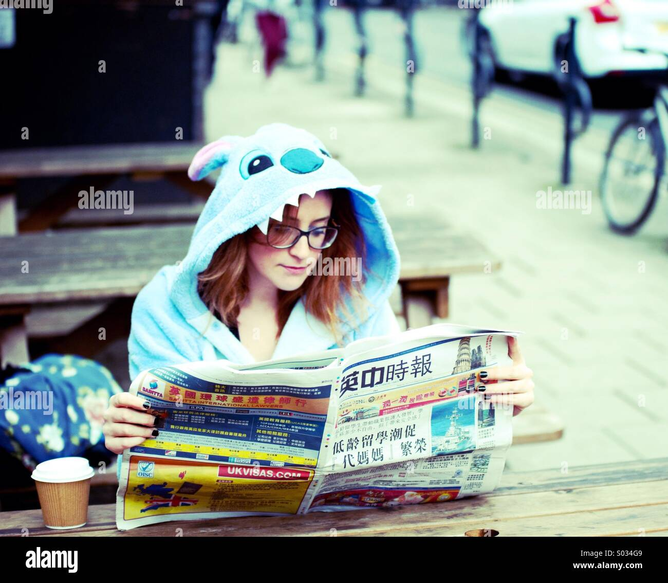 Woman in Stitch costume reading a Chinese newspaper - Stock Image
