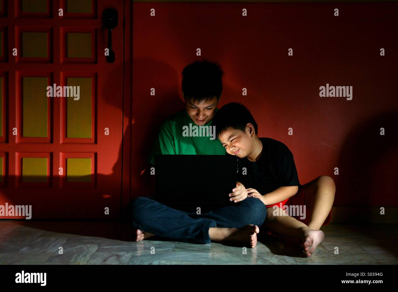 Young asian kids, or siblings with a laptop computer in an empty living room - Stock Image