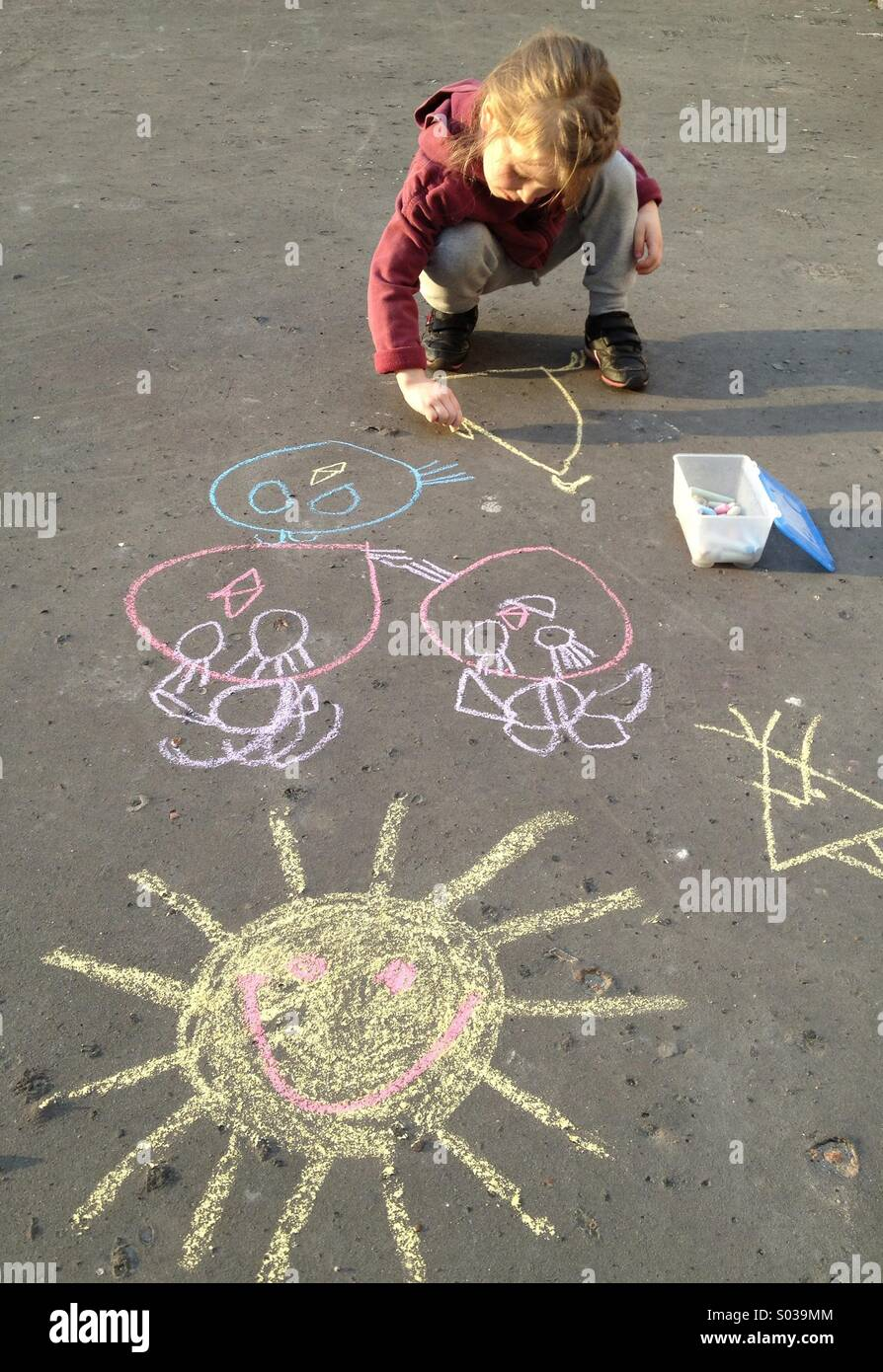 Little girl drawing with chalk - Stock Image