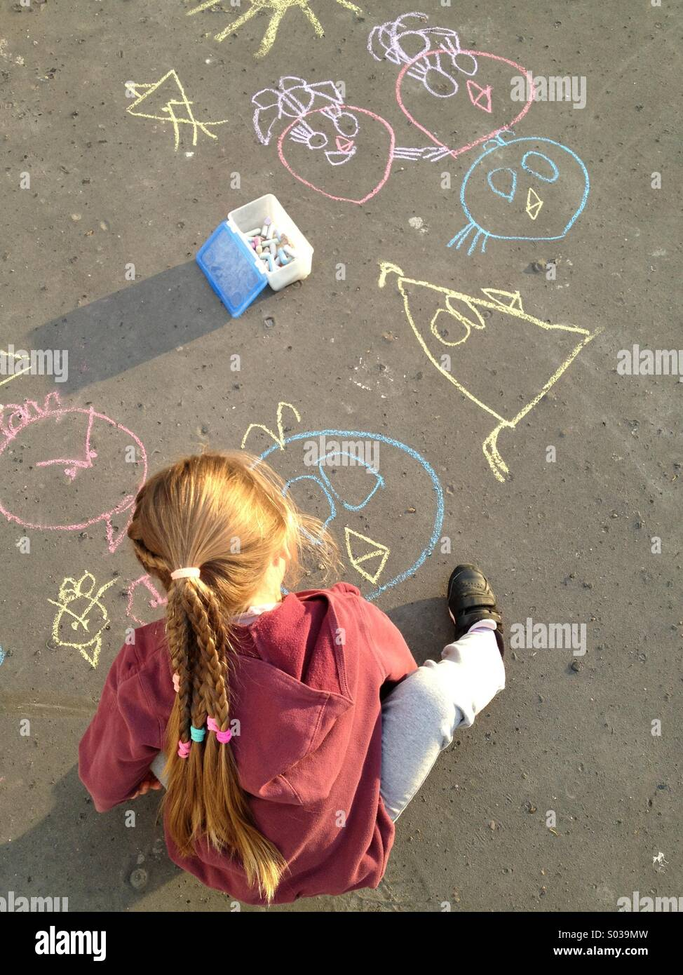 Child drawing with chalk on asphalt - Stock Image