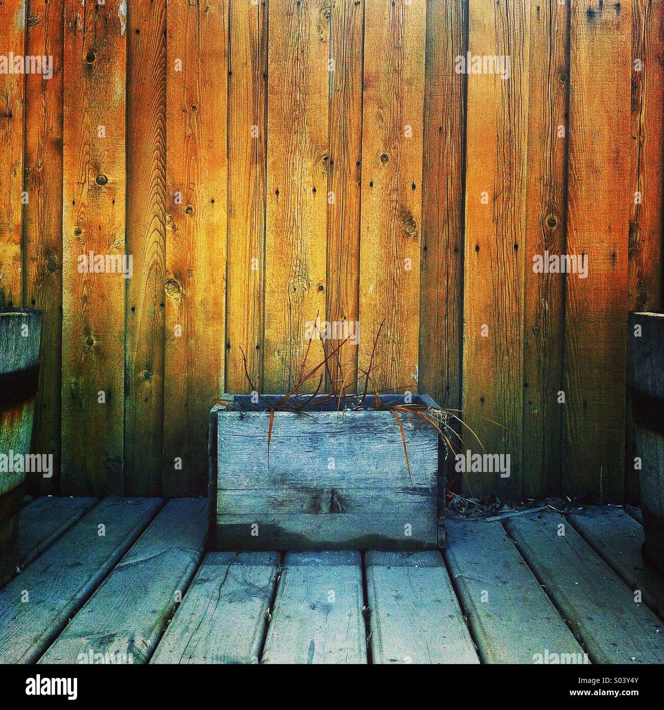 Wooden planter in front of fence - Stock Image