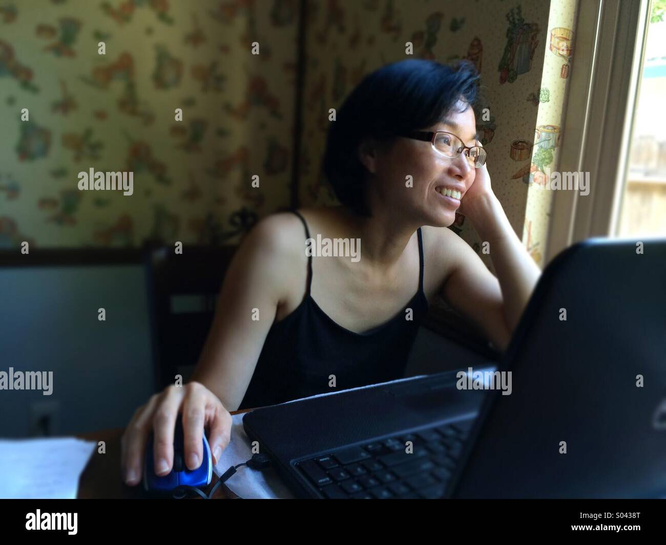 Asian woman smiling and looking out a window while using a laptop computer at home - Stock Image