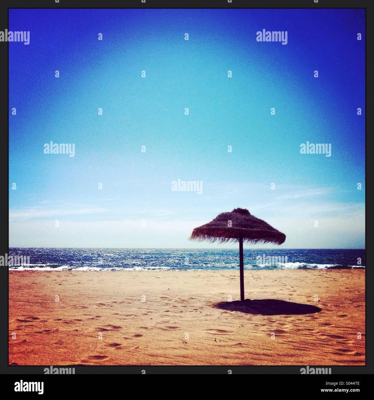 Parasol on Portuguese beach - Stock Image