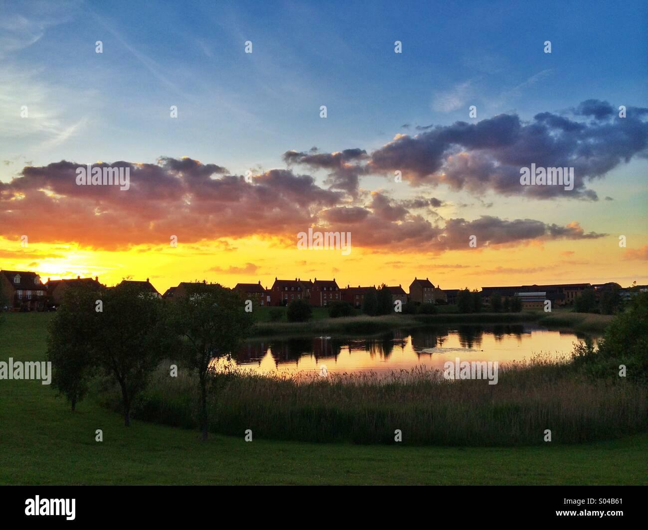 Houses overlooking lake at sunset, Hampton Vale, Peterborough, UK - Stock Image