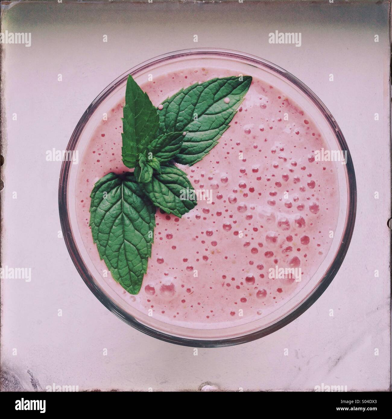 A strawberry smoothie with mint leaves is seen. - Stock Image