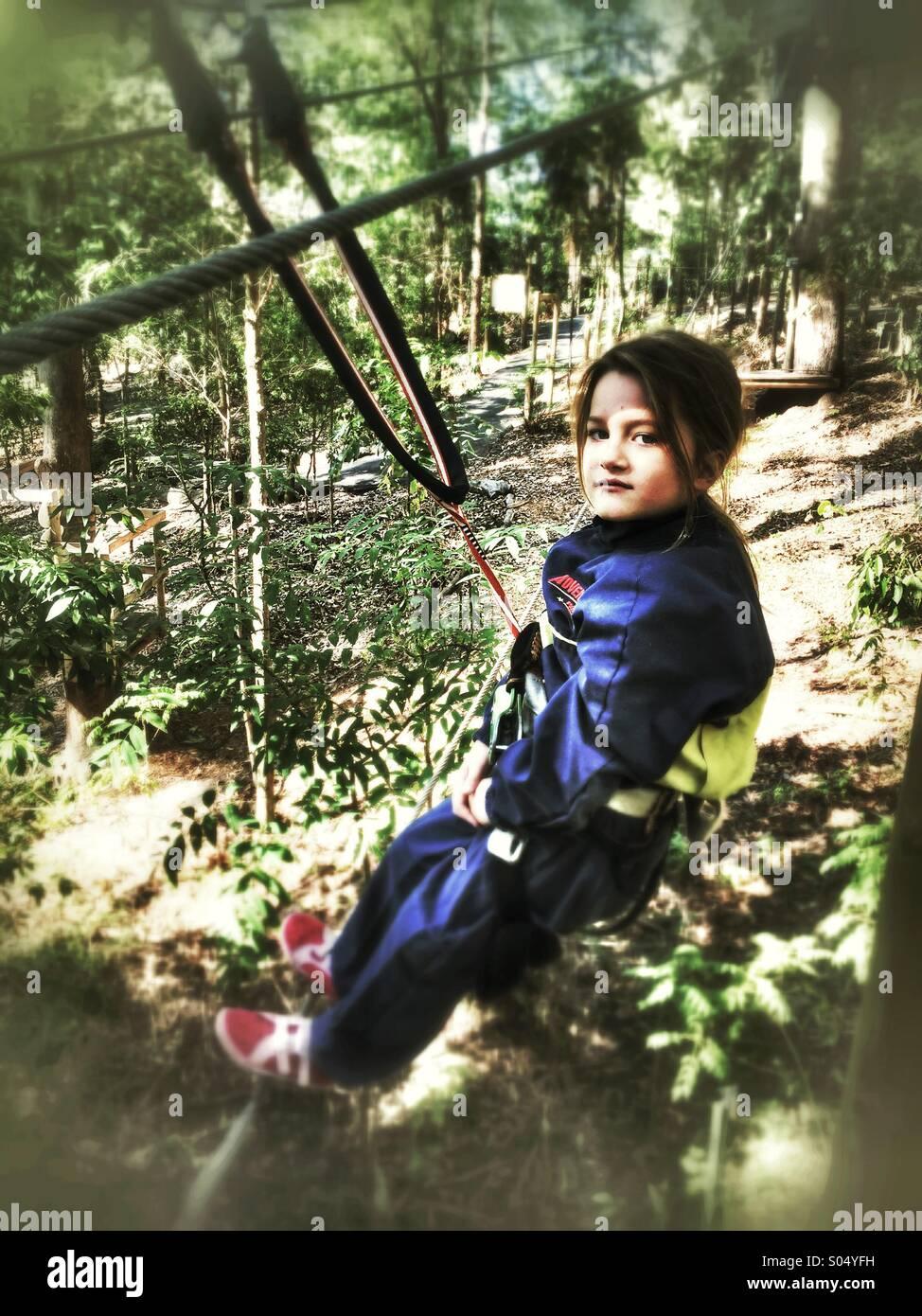 Young girl tree climbing - Stock Image