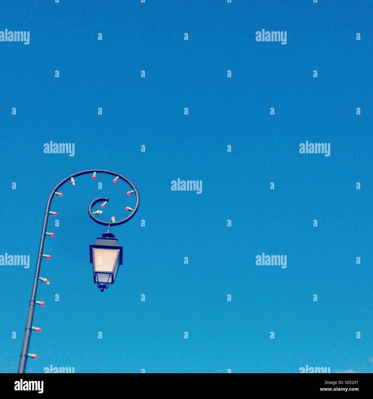 Street light against blue sky - Stock Image
