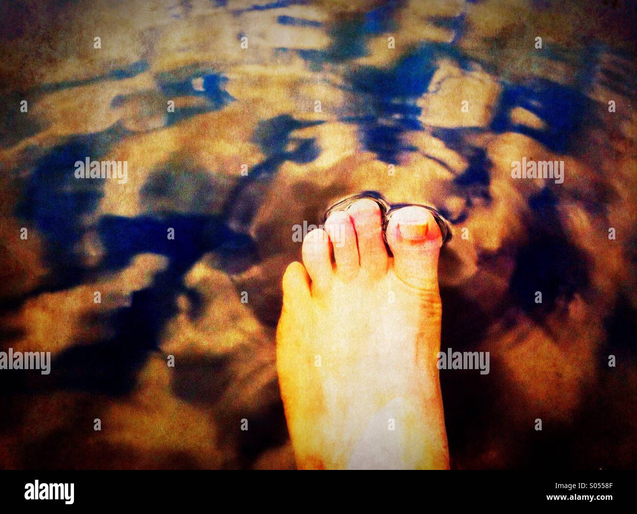 Dipping foot to a lake - Stock Image