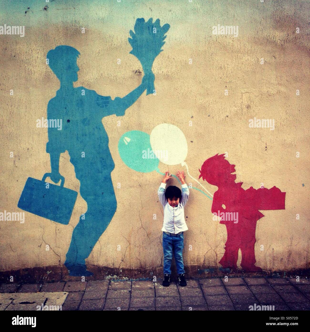 Little boy facing camera tries to reach for the balloon painted on the wall Stock Photo