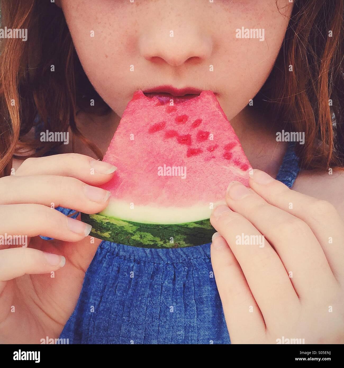Girl eats watermelon. - Stock Image