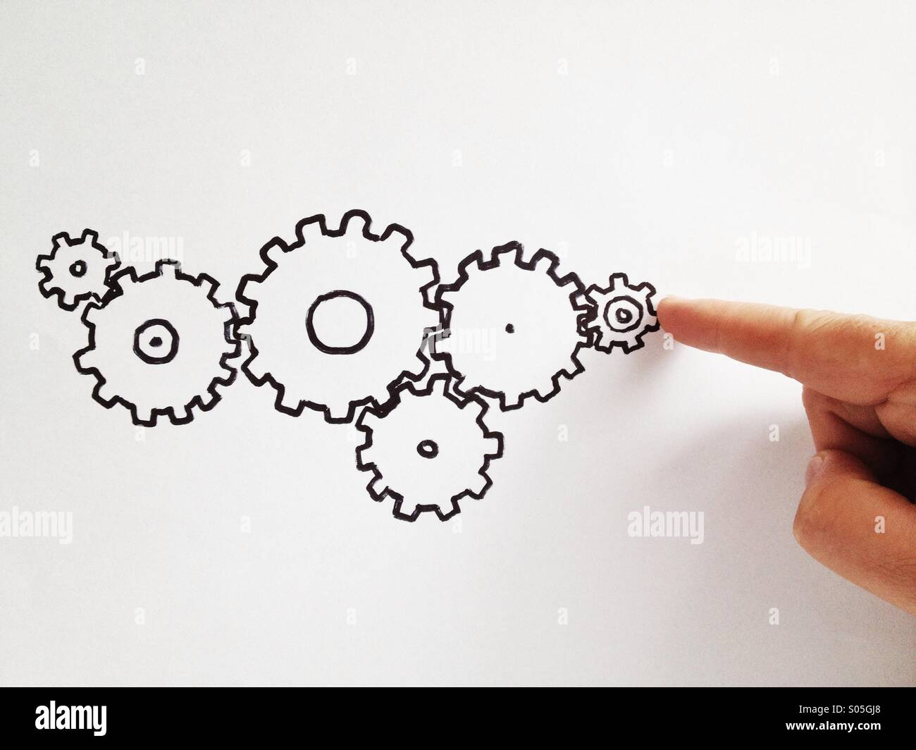 Finger moving gears - Stock Image