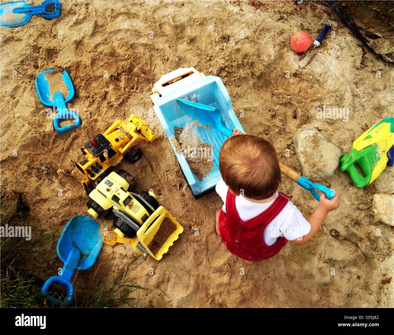 Toddler boy plays with a shovel and trucks in a large sandbox. - Stock Image