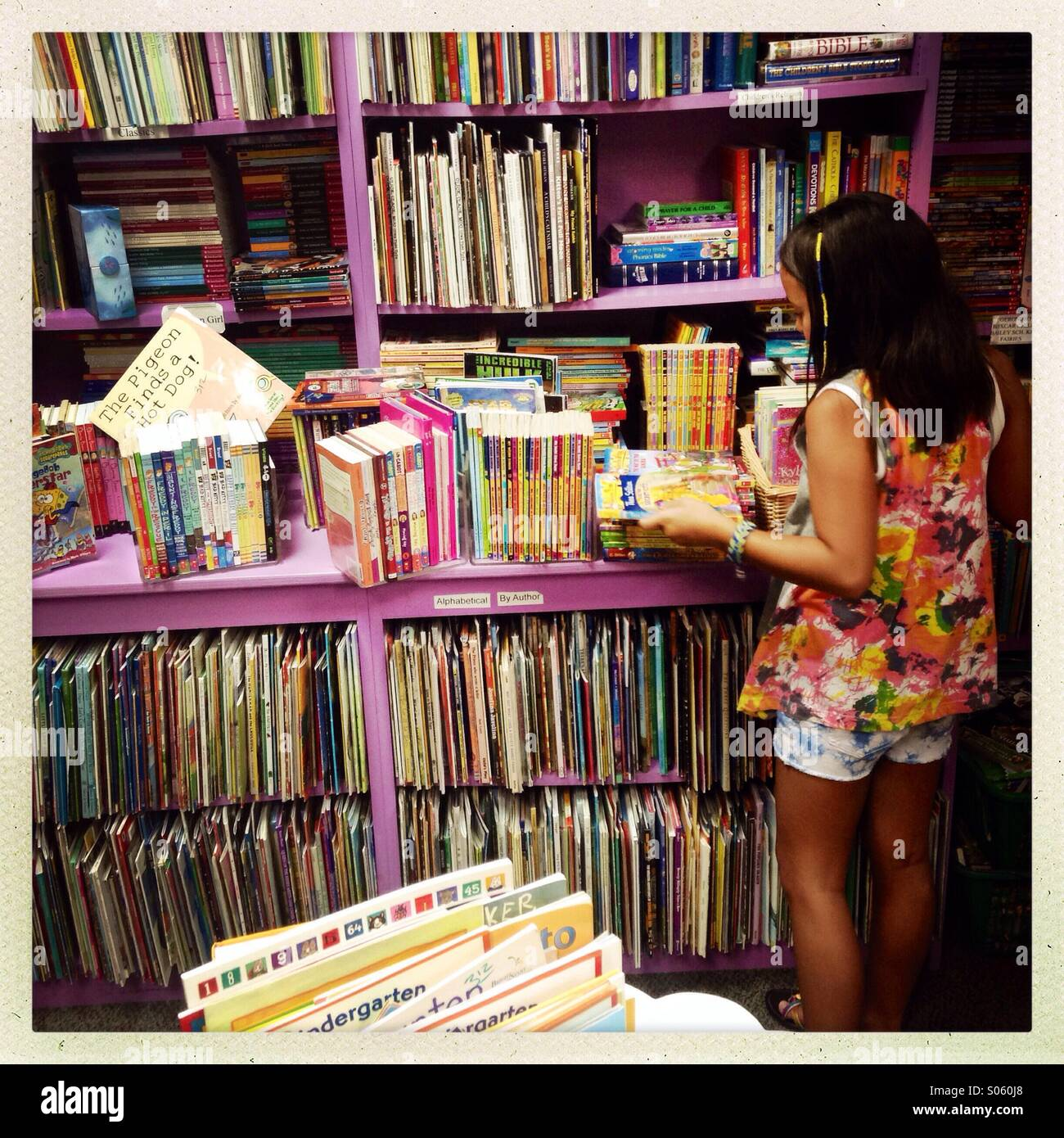 Asian girl shopping for a book - Stock Image