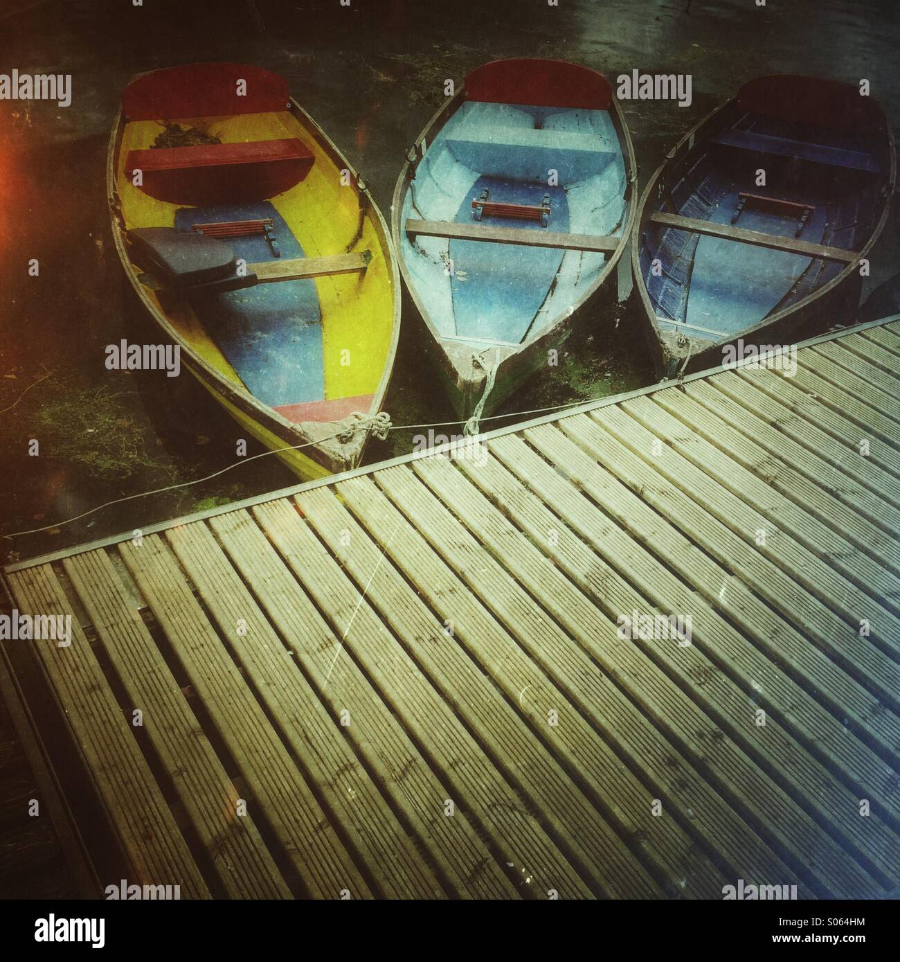 Three colourful rowing boats tied up onto a wooden jetty - Stock Image