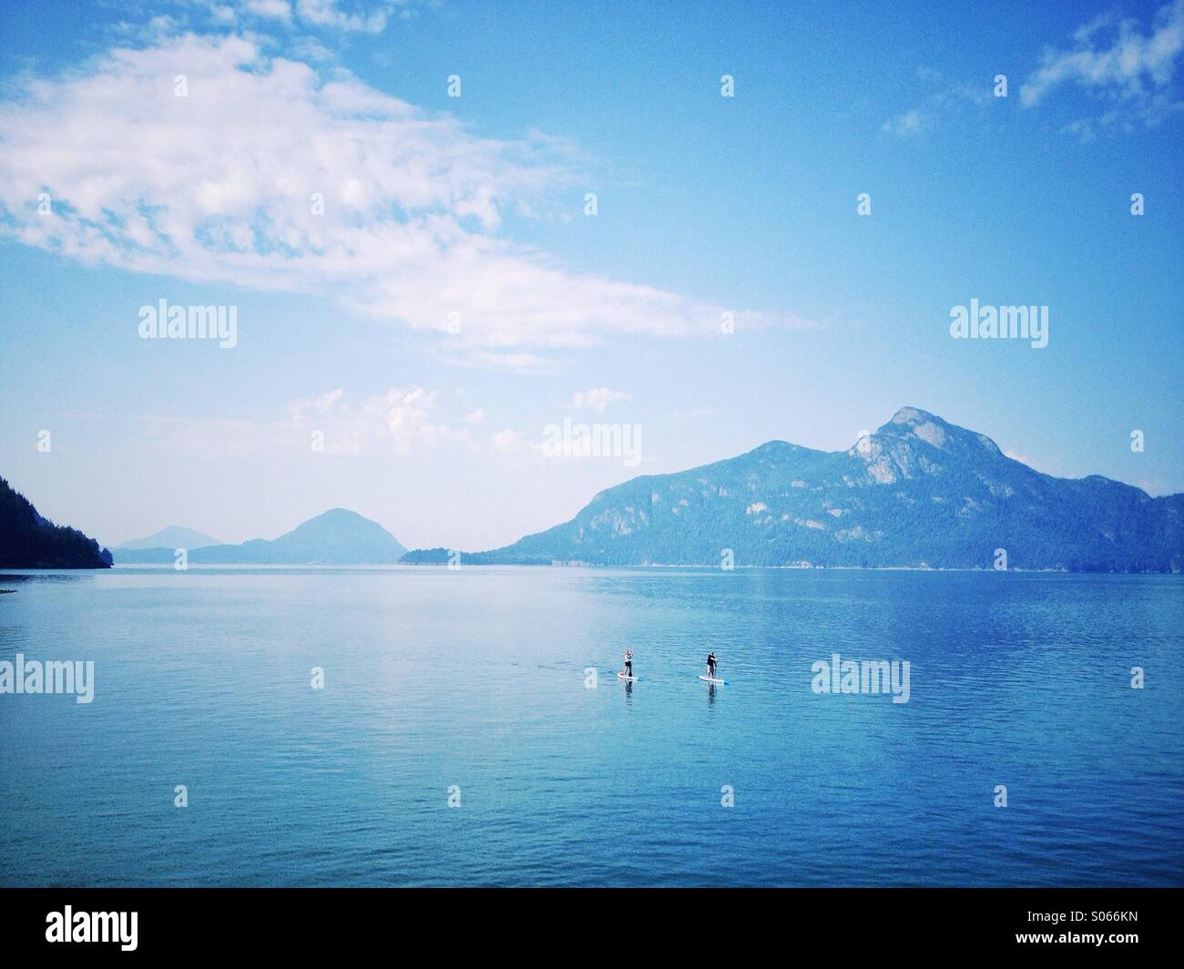 Stand up paddle boarders on Howe Sound, British Columbia with mountain background. - Stock Image