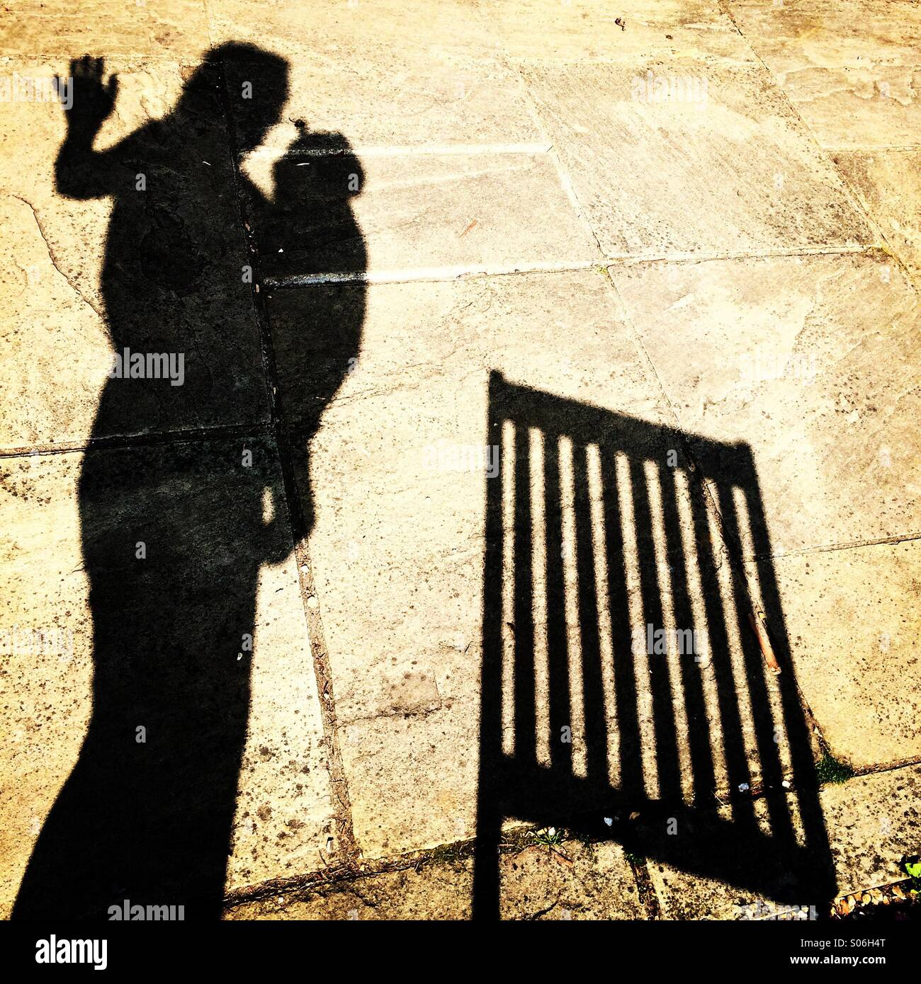 Silhouette of a mum and her baby in a sling next to a deck chair - Stock Image