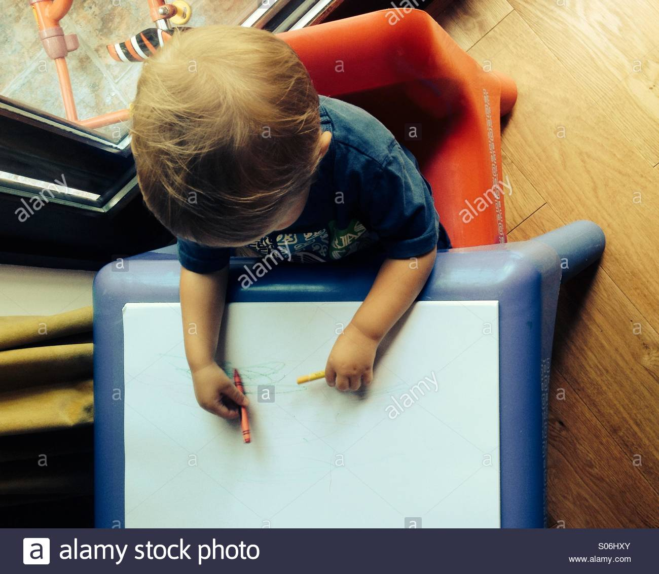 Toddler drawing first scribbles on paper with crayons - Stock Image