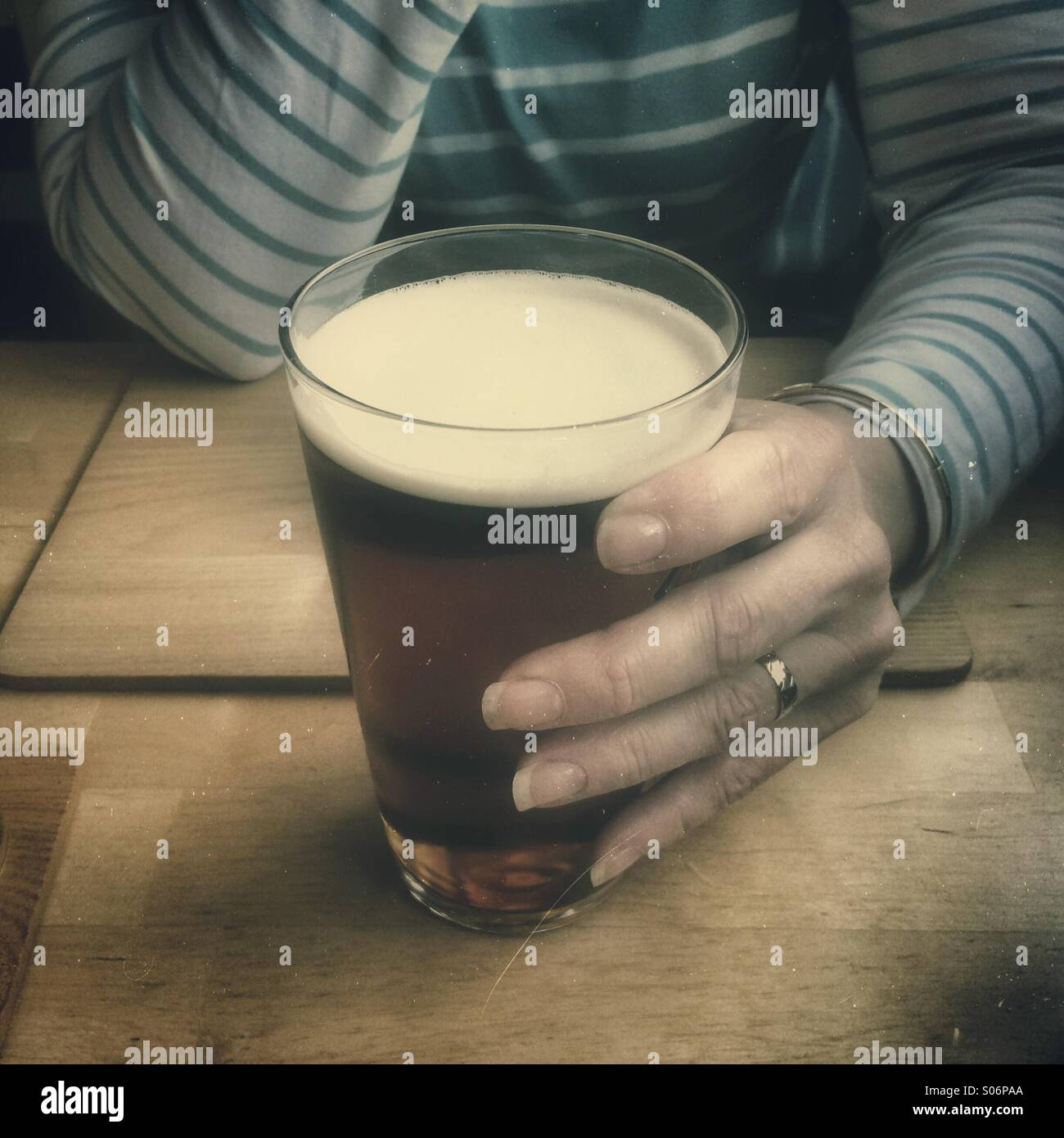 Woman sitting alone at table in public house bar, holding pint glass of beer - Stock Image