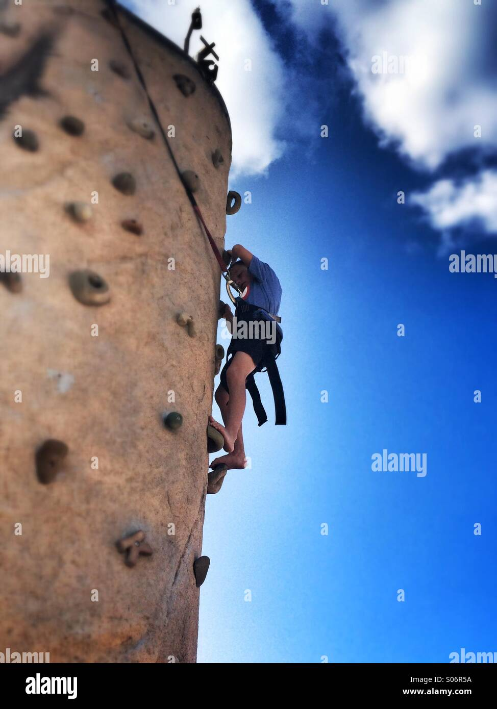 A young boy attempts to climb a rock wall - Stock Image