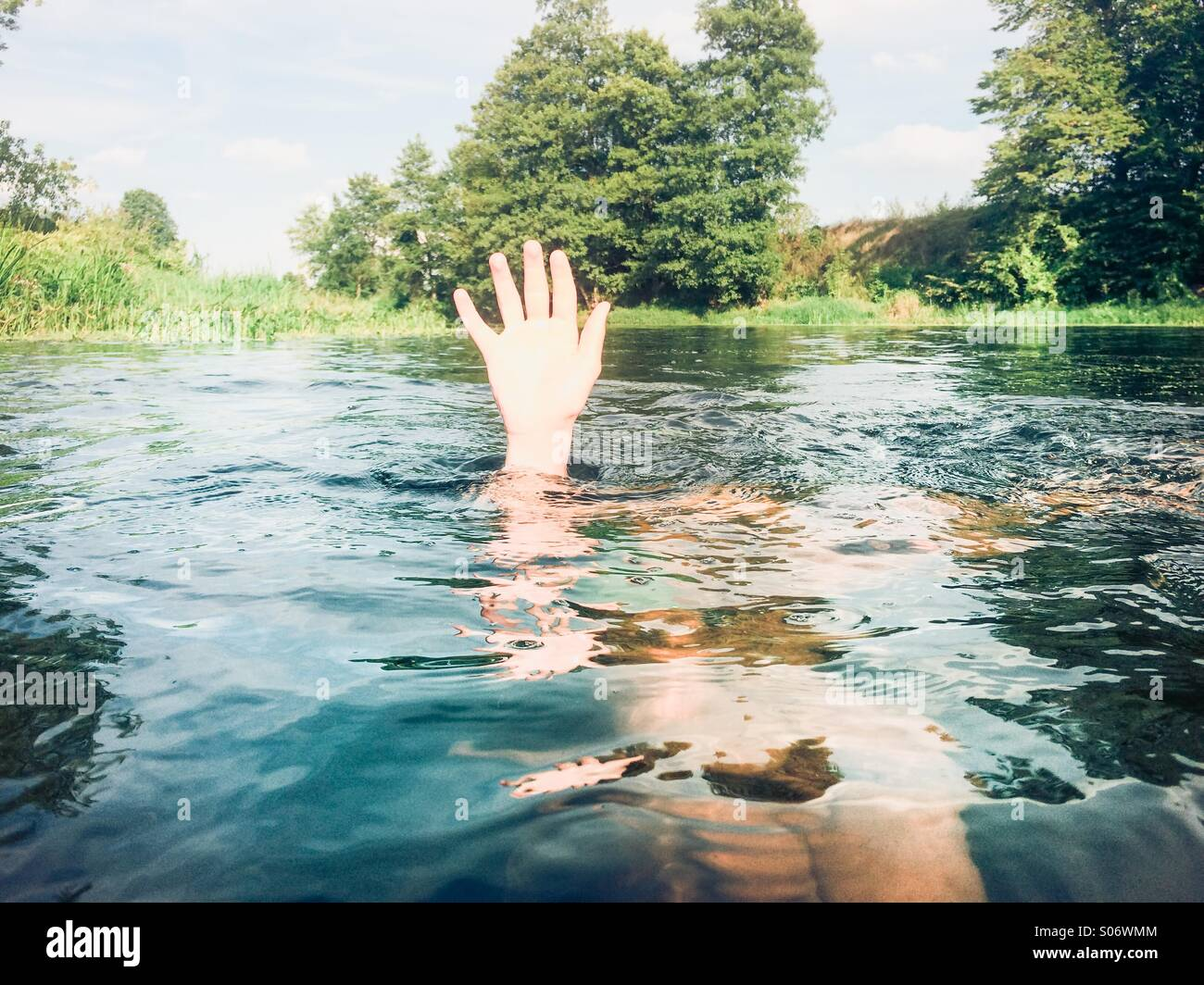 Boy submerged in a pure river keeping his hand above the water - Stock Image