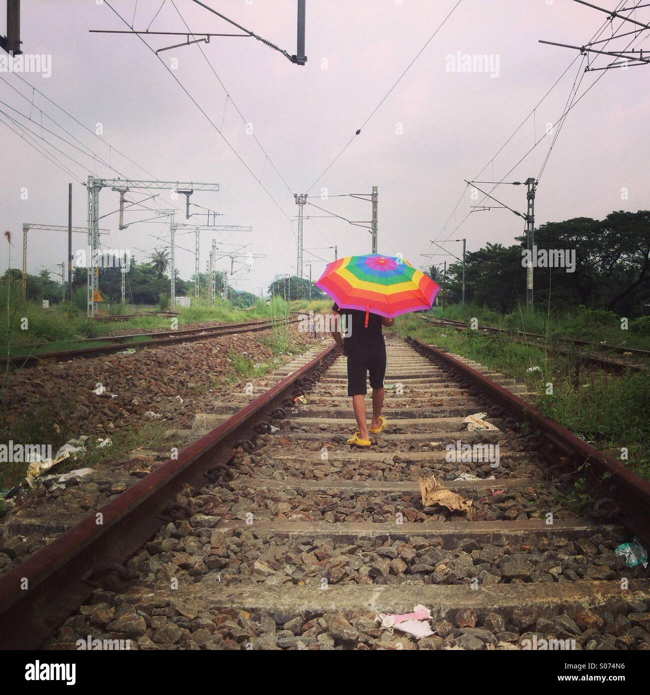 Young Indian boy walking alone through a railway track - Stock Image