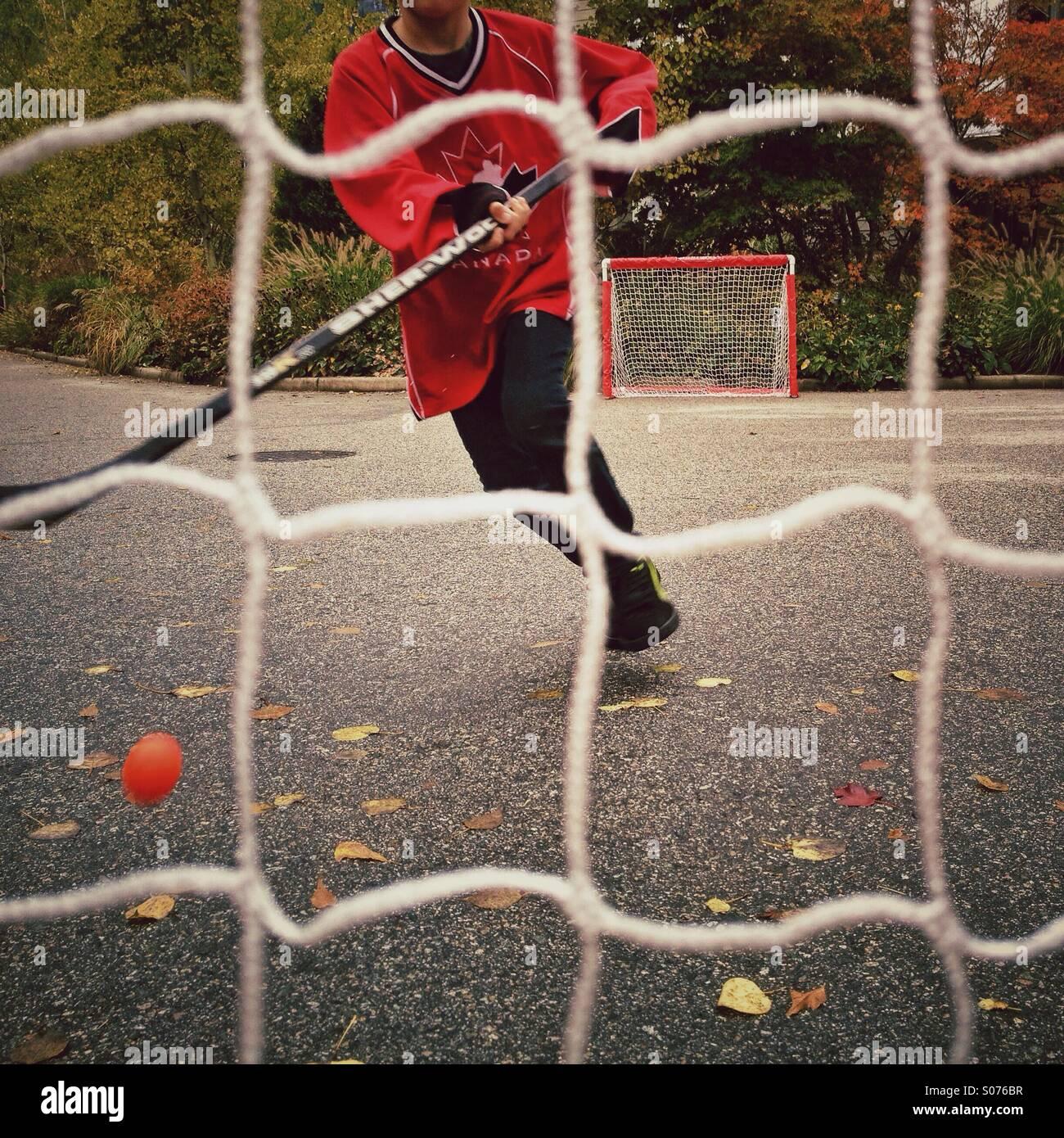 Boy playing street hockey - Stock Image