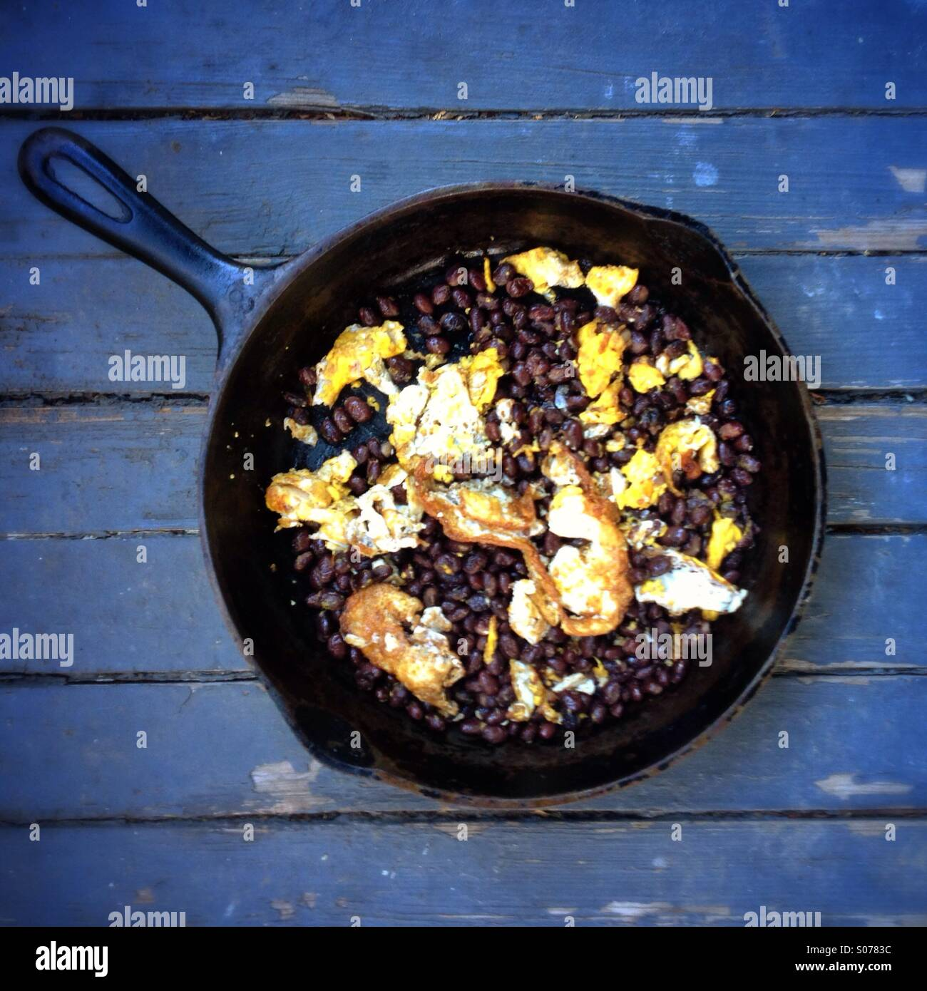 Black beans and eggs in an iron skillet - Stock Image